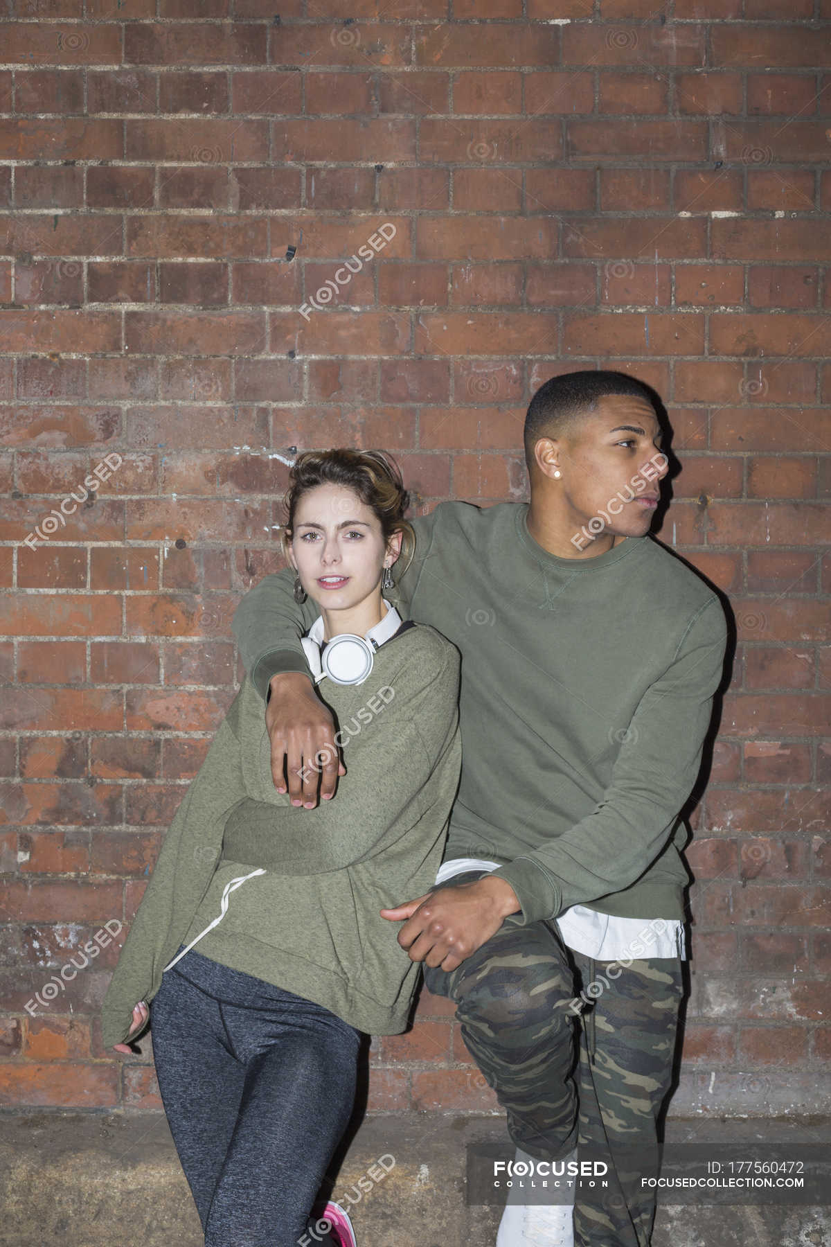 Stylish Young Couple Leaning Against Brick Wall At Night