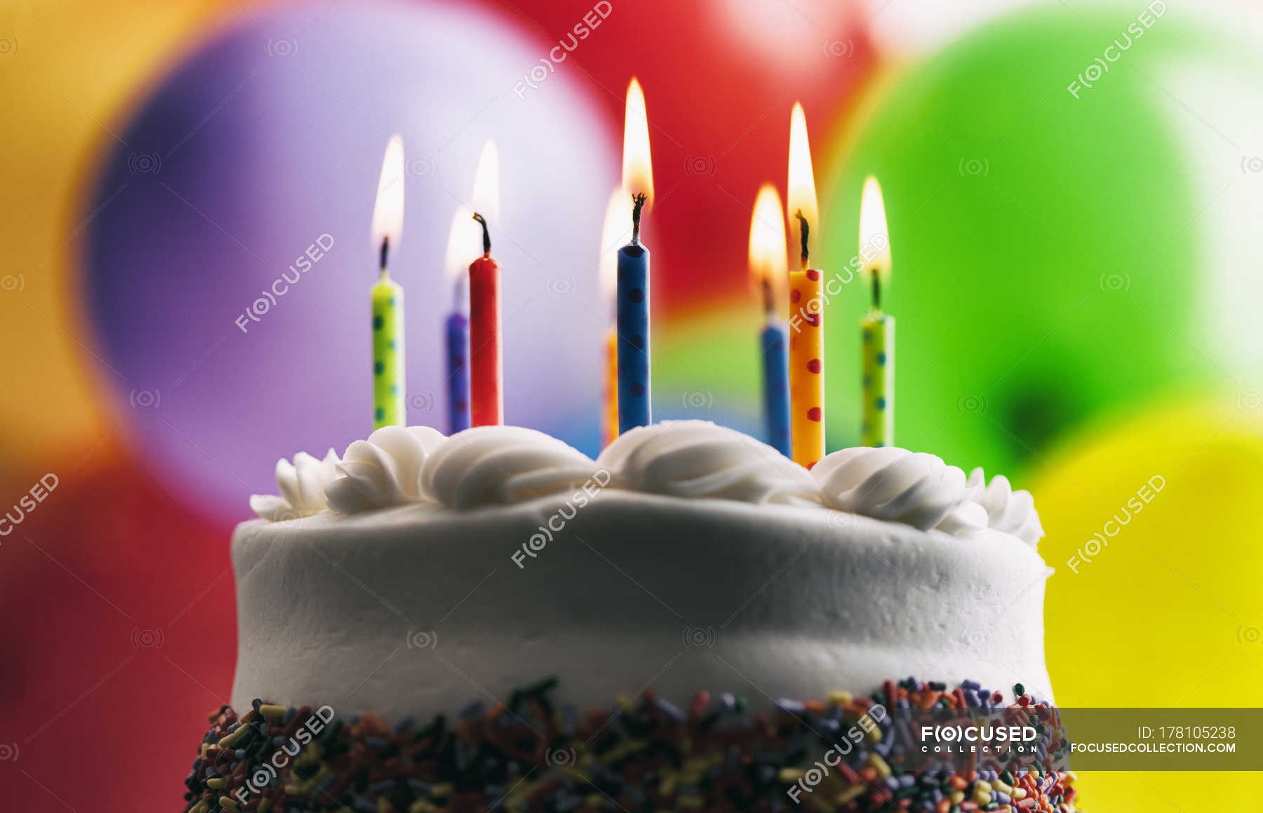 Lighted Birthday Candles On Cake In Front Of Balloons Stock Photo