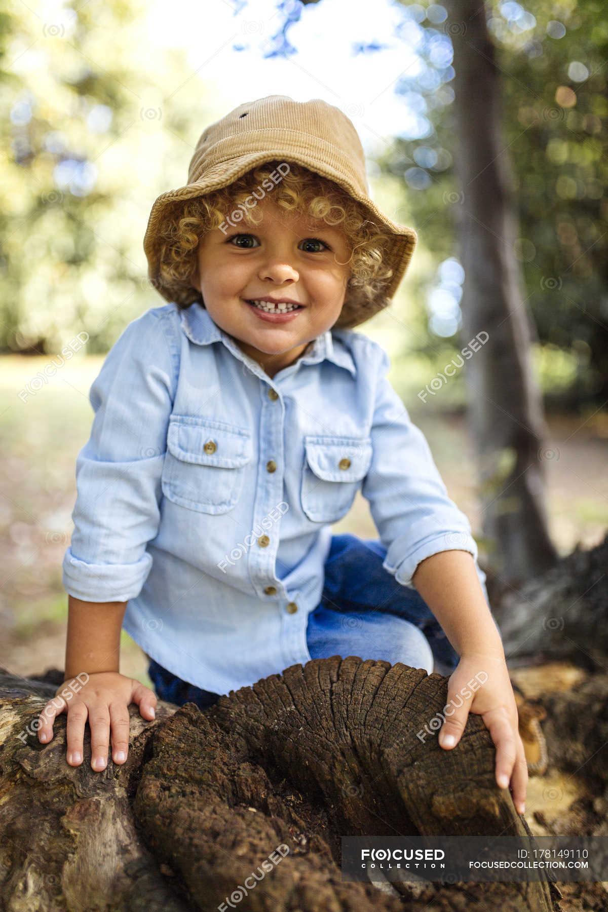 c233366d20b Portrait of smiling blond little boy wearing hat sitting on dead wood —  Stock photos