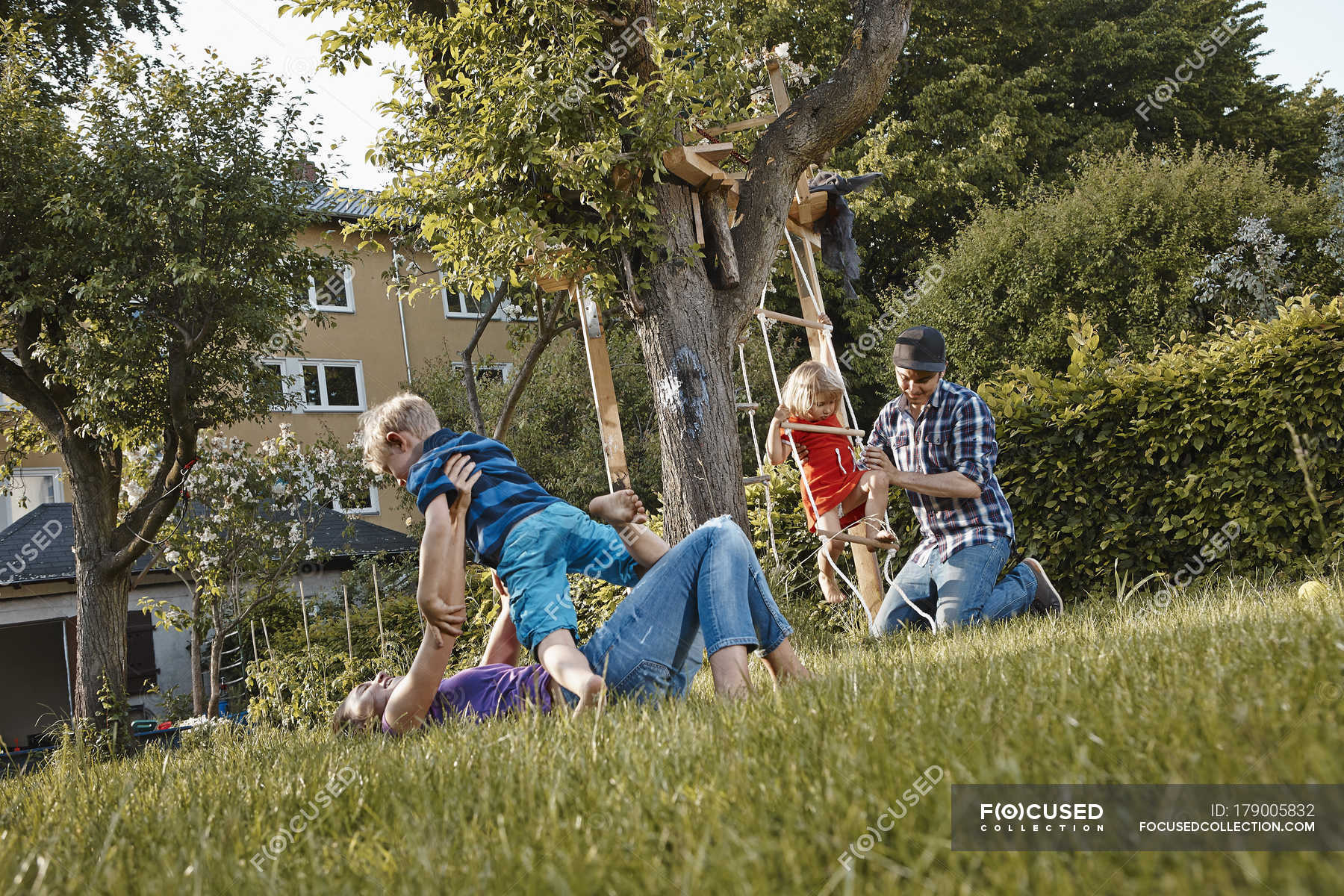 Happy family playing in summer garden — Stock Photo | #179005832