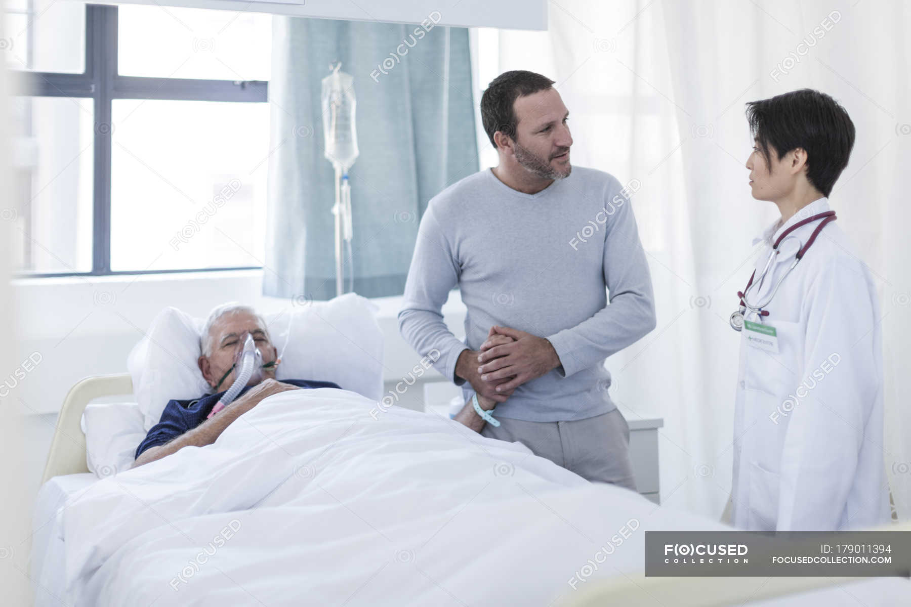 Doctor talking to man visiting patient in hospital — Stock Photo ...