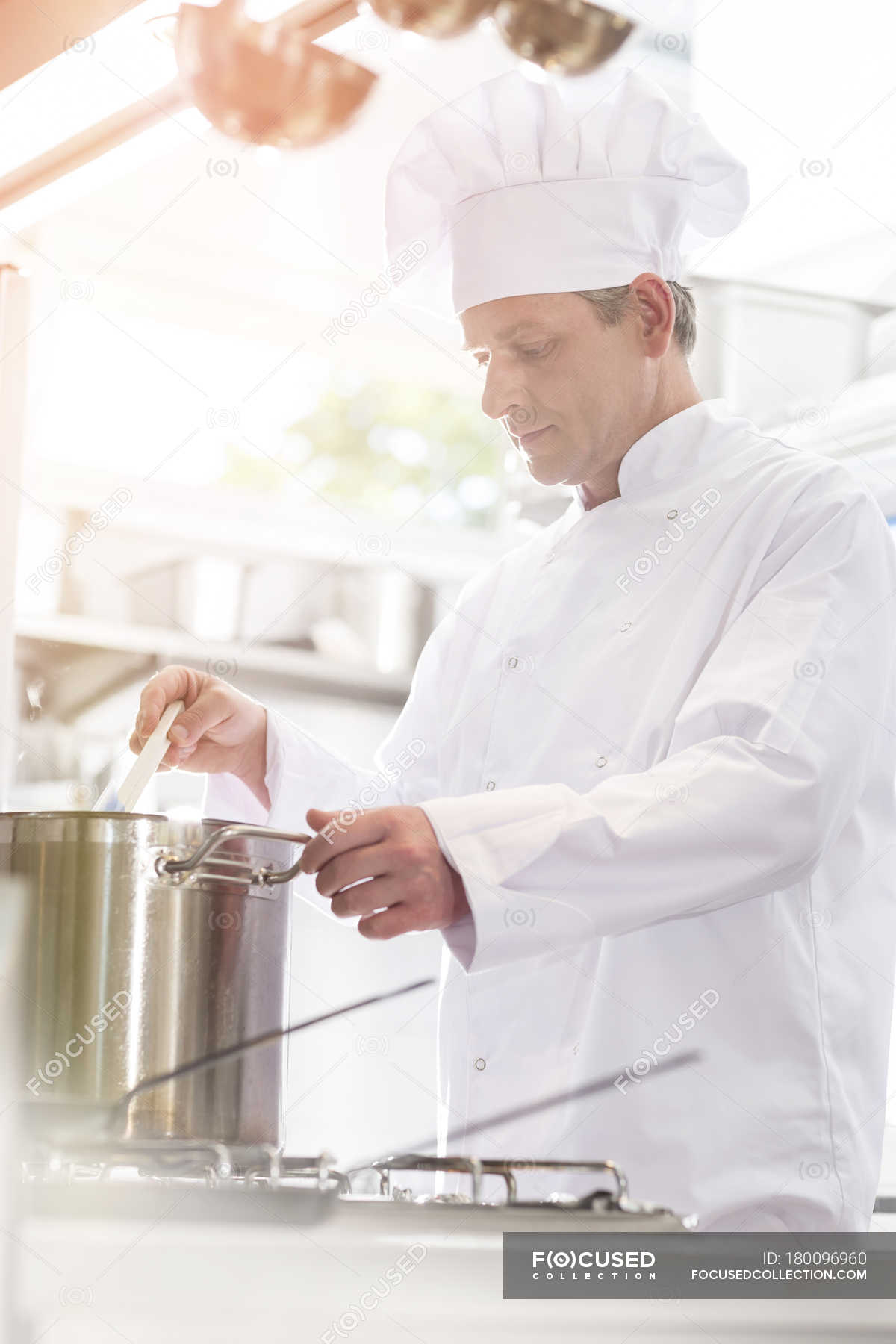 Chef in kitchen cooking in pot, side view — Stock Photo | #180096960