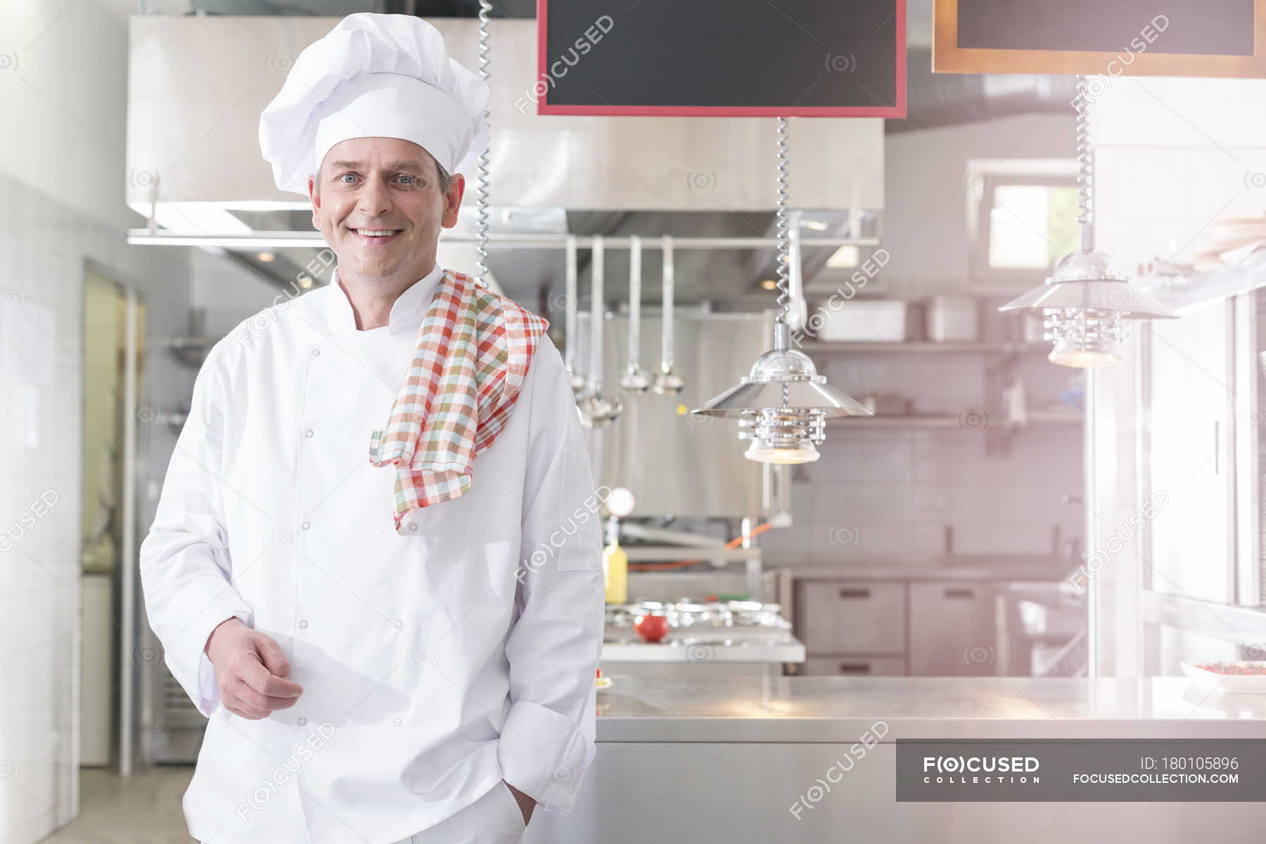 Smiling chef in kitchen with towel on shoulder — one person ...