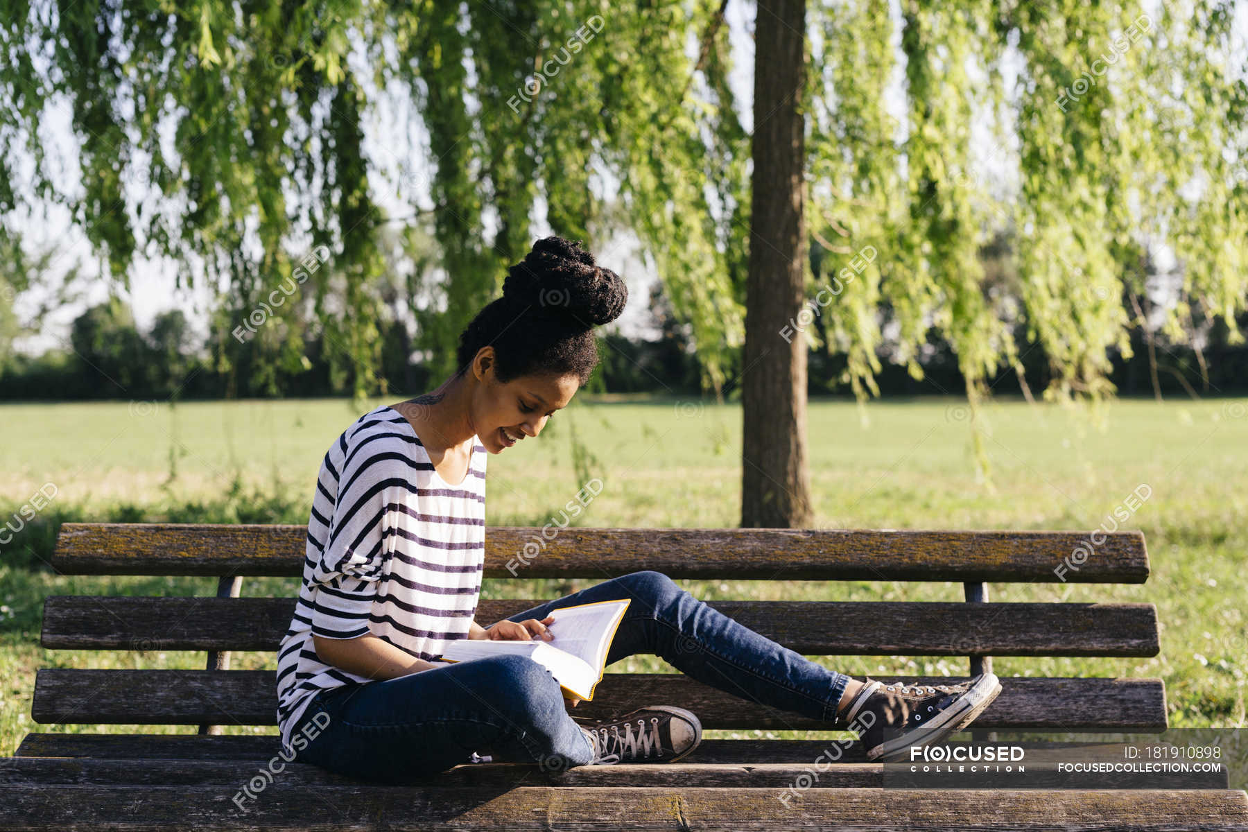 Woman Thoughtfully Sitting On Park Bench Stock Photo