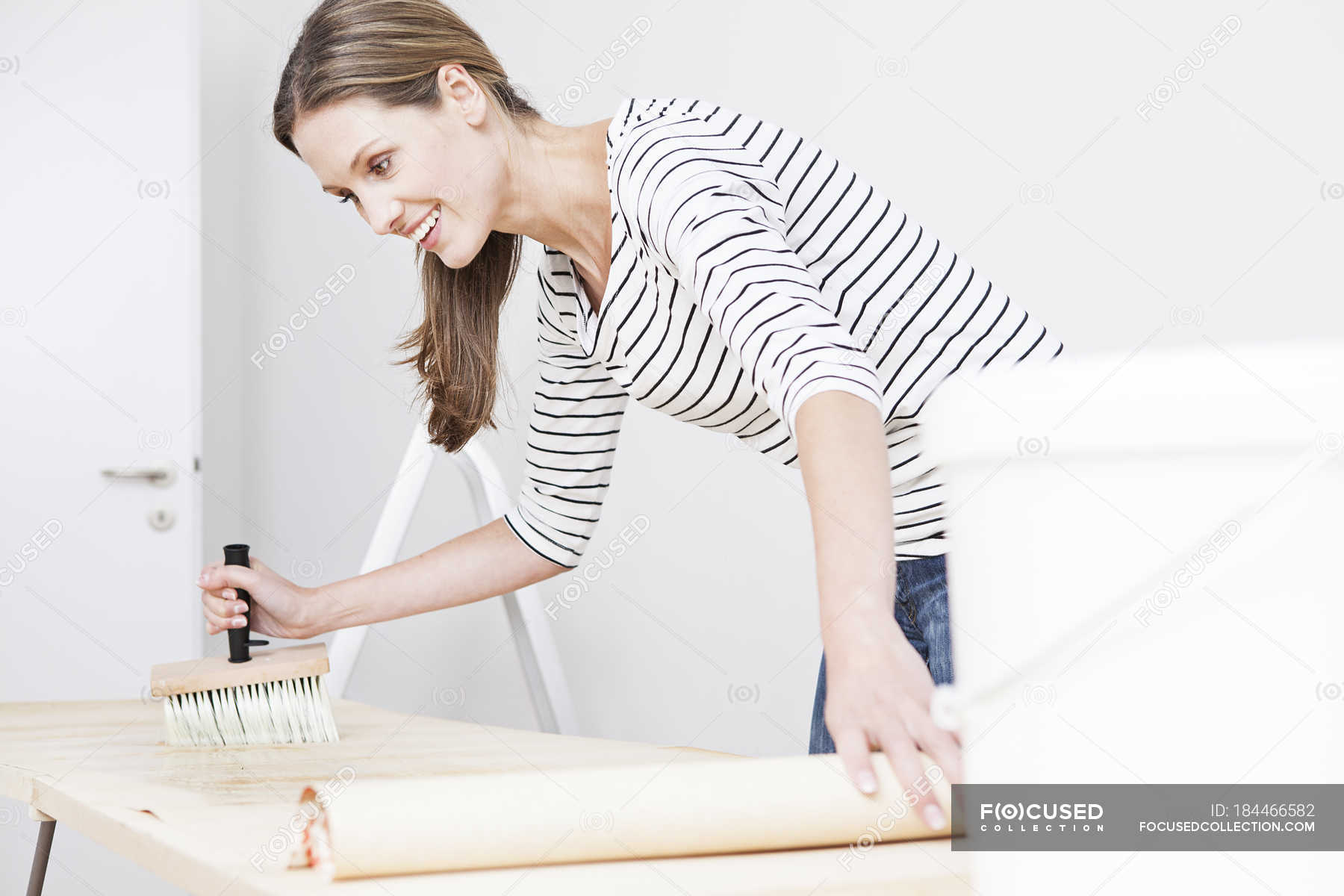 Woman applying glue on wallpaper