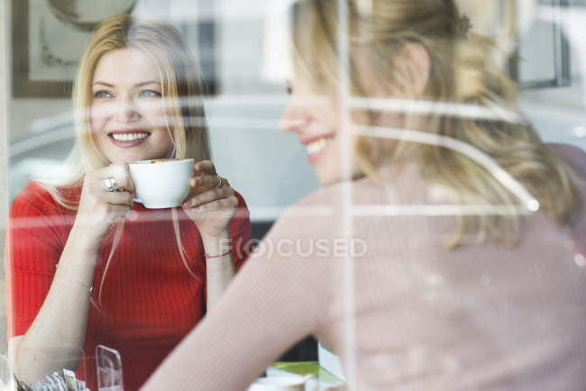 Smiling young women in cafe — Stock Photo