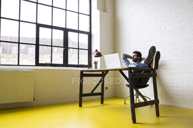 Giovane seduta con i piedi in su — Foto stock