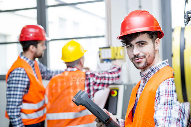 Portrait of confident man wearing hard hat in factory — Stock Photo