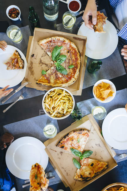 Friends eating pizza and French fries — Stock Photo