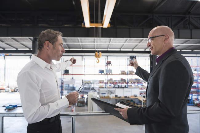 Businessmen interacting in factory shop floor — Stock Photo