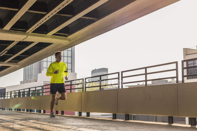 Hombre corriendo en el nivel de estacionamiento - foto de stock