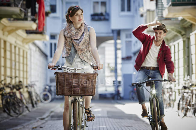 Germany, Hamburg, St. Pauli, Couple exploring the city on their bicycles — Stock Photo