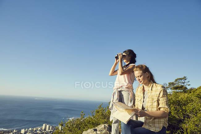 Women with map and binoculars overlooking sea — Stock Photo