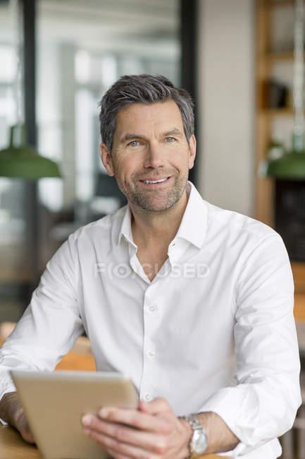 Empresário com tablet, olhando para a câmera — Fotografia de Stock