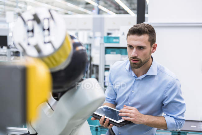 Man using tablet examining assembly robot — Stock Photo