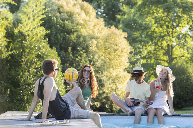 Amigos relaxantes à beira da piscina — Fotografia de Stock