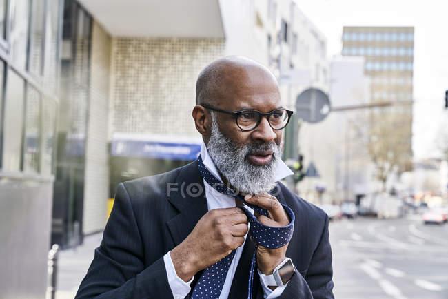 Homme d'affaires liant ex aequo dans la rue — Photo de stock
