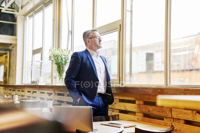 Uomo d'affari che osserva dalla finestra nella caffetteria — Foto stock