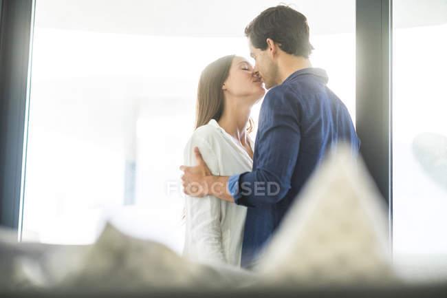 Couple embrasser à fenêtre — Photo de stock