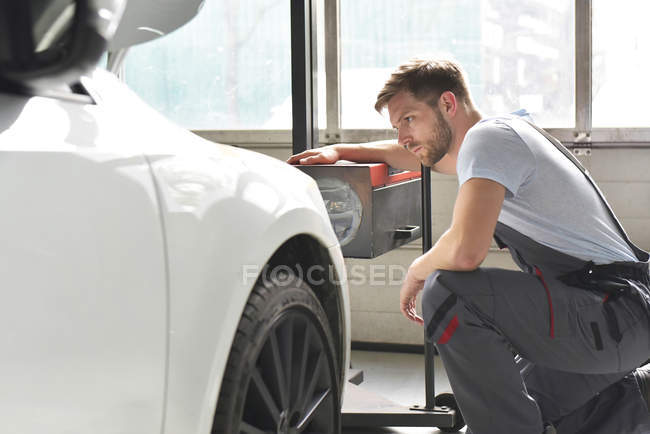 Car mechanic adjusting headlights — Stock Photo