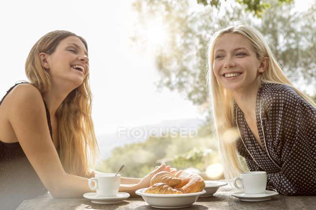 Laughing friends having breakfast — Stock Photo