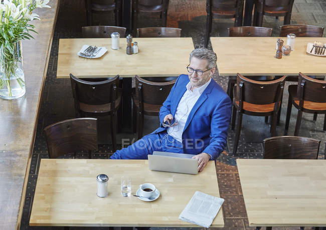 Businessman sitting in cafe with laptop — Stock Photo