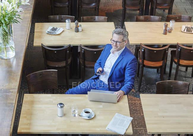 Бизнесмен, сидя в кафе с ноутбуком — стоковое фото