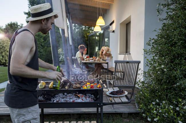 Людина в гриль барбекю з друзями — стокове фото