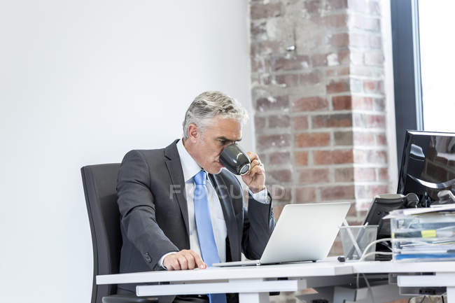 Businessman sitting and drinking coffee — Stock Photo