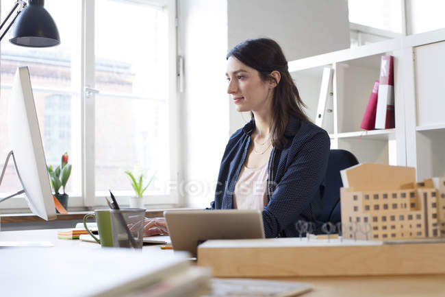 Woman working on computer in modern office — Stock Photo