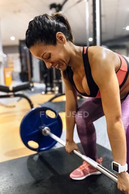 Woman lifting barbell — Stock Photo