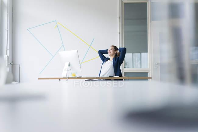 Geschäftsfrau sitzt mit den Händen hinter dem Kopf — Stockfoto
