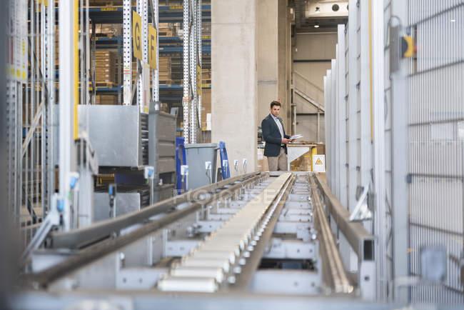 Бизнесмен на конвейер завода — стоковое фото