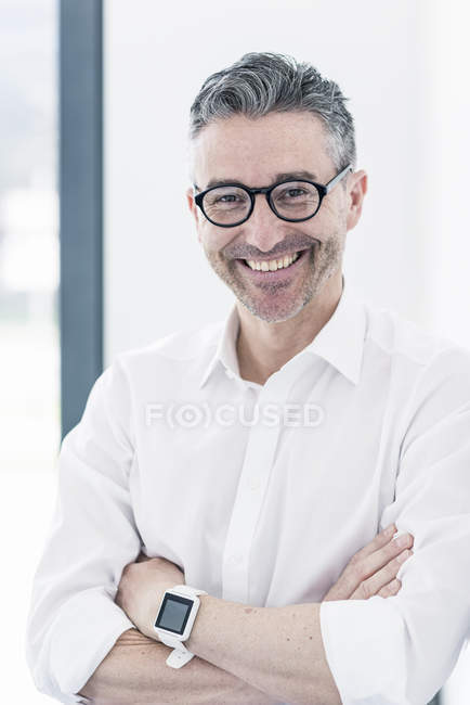 Businessman standing in office with arms crossed — Stock Photo