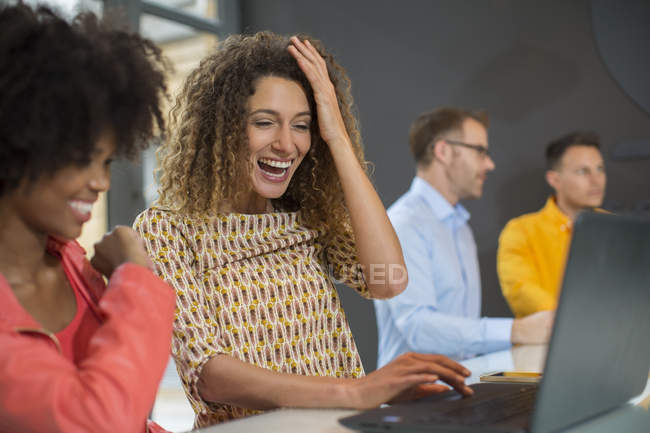 Women in office sharing laptop — Stock Photo