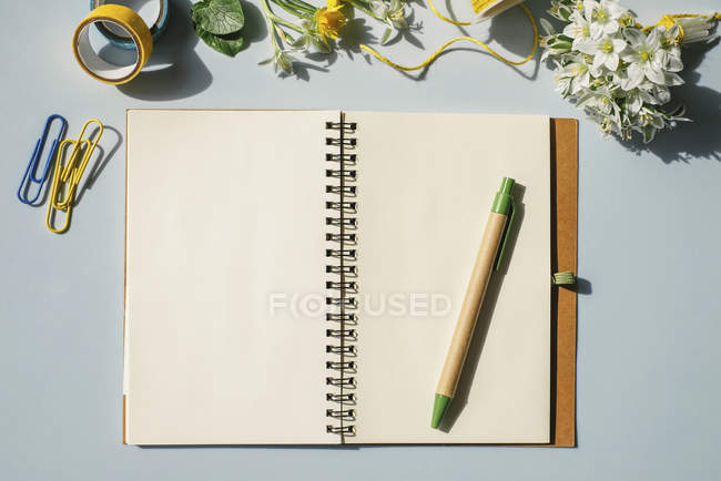 Notebook with office supplies and flowers — Stock Photo