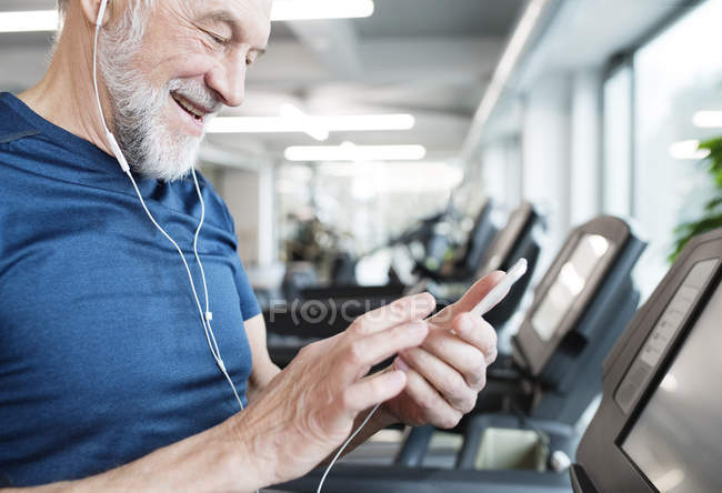 Ältere Mann mit Smartphone in Turnhalle — Stockfoto