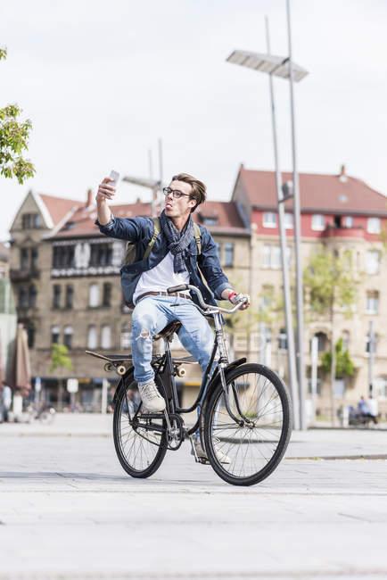 Homme d'équitation vélo et prise selfie — Photo de stock