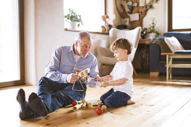 Дідусь і онук, граючи з іграшками — стокове фото