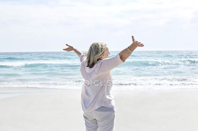 Femme debout sur la plage — Photo de stock