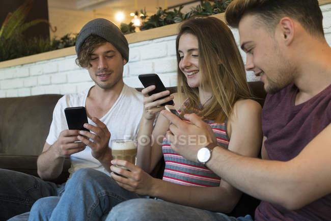 Três amigos usando telefones celulares — Fotografia de Stock