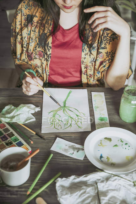 Woman painting plant with watercolors — Stock Photo