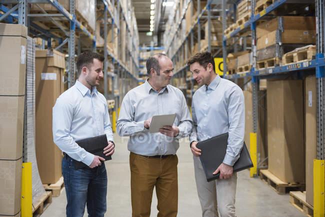 Hommes parlent dans l'entrepôt de l'usine — Photo de stock