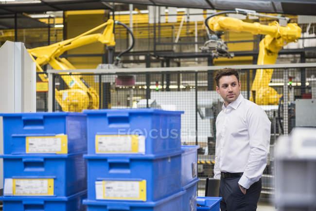 Бизнесмен, стоящий на заводе — стоковое фото