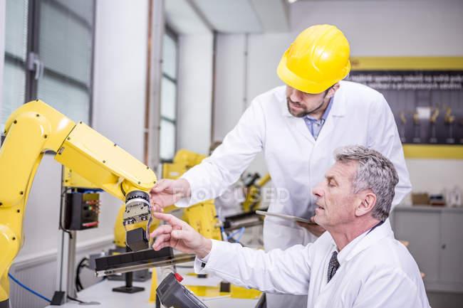 Інженери, вивчаючи Промисловий робот — стокове фото