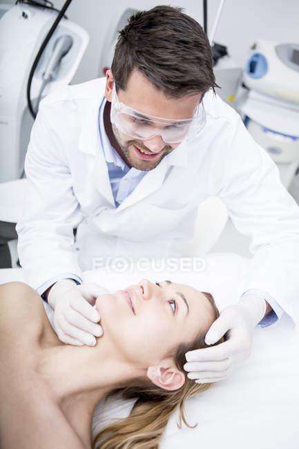 Doctor looking at woman at surgery — Stock Photo