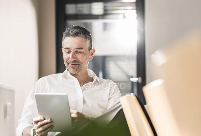 Businessman sitting in office and using tablet — Stock Photo