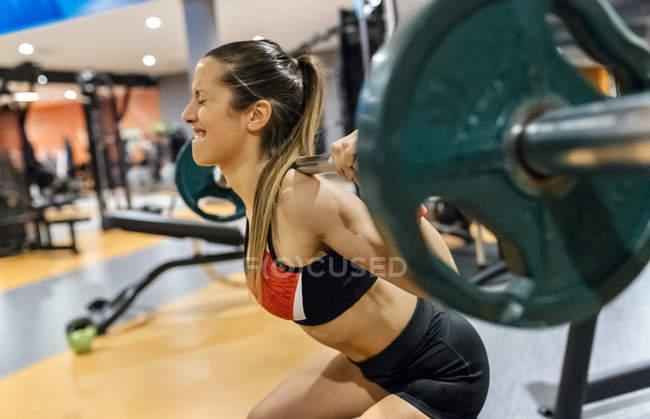 Женщина поднимает штангу — стоковое фото