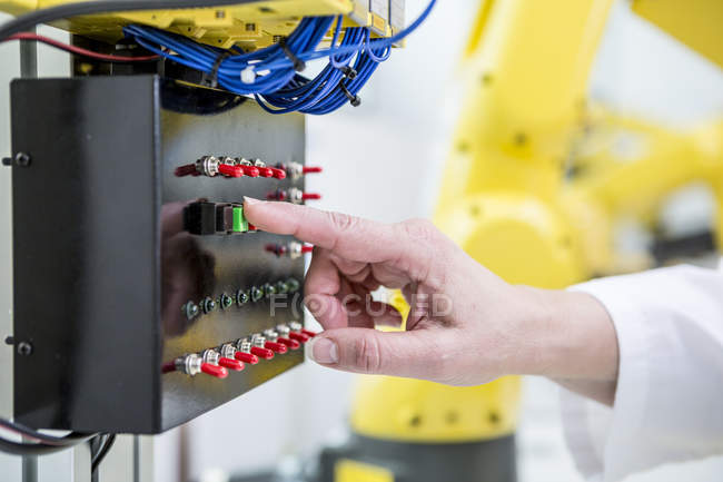 Close-up of woman switching on switch in factory — Stock Photo