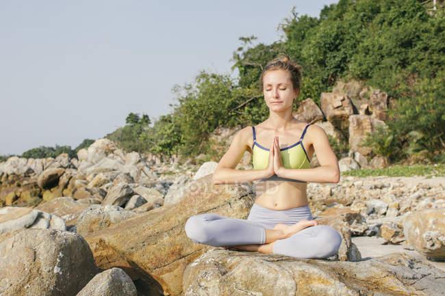 Женщина, сидящая на лотосном сидении, медитируя на пляже — стоковое фото